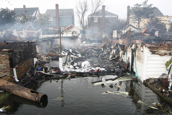 Stephen Yang, October 30th, 2012 - Queens, NY: The scene at 130th St. and Newport Ave. in Rockaway where many houses were burned down after Hurricane Sandy hit the area. Locals milled about looking for reminders of their houses in a daze