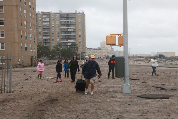 Stephen Yang, October 30th, 2012 - Queens, NY: A family evacuates, walking with their possessions down the Rockaway boardwalk near Beach 105th St. after floods and heavy wind from Hurricane Sandy hit the Rockaways.
